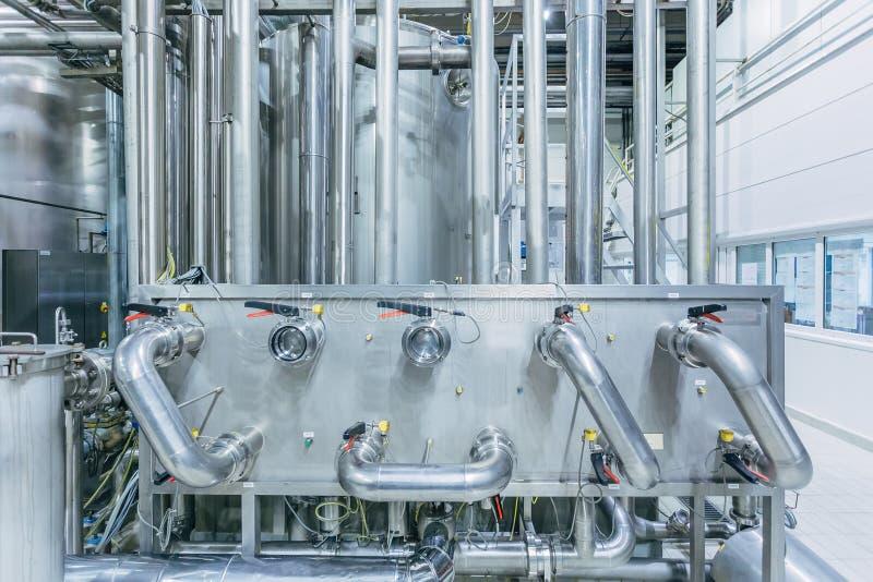 Tini d'acciaio industriali collegati dalla conduttura immagini stock
