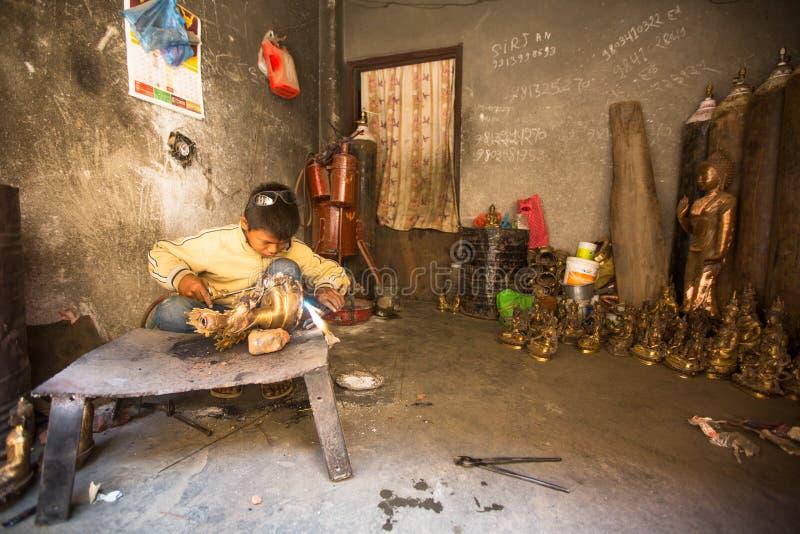 Tinman nepalese che lavora nella sua officina, in Bhaktapur, il Nepal fotografie stock