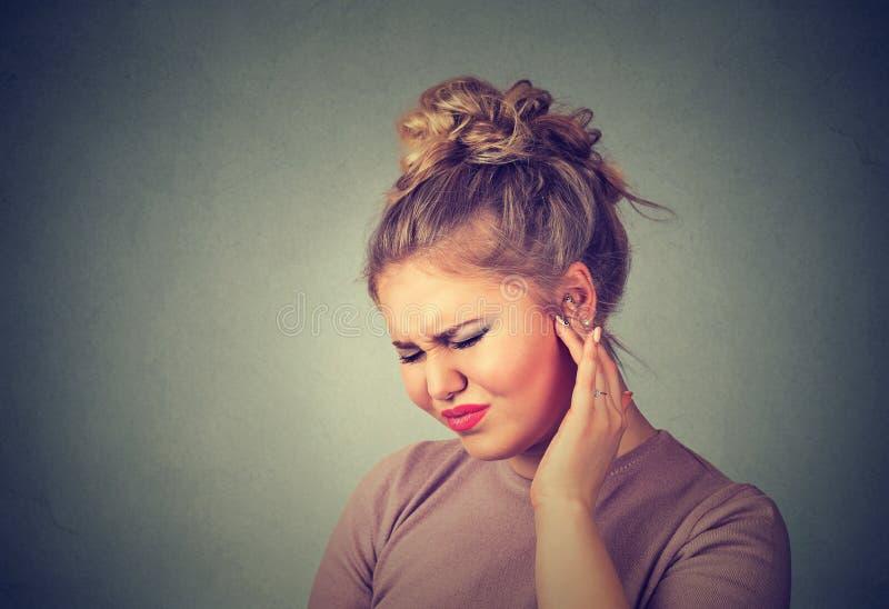 tinnitus Больная женщина имея боль уха касаясь ее тягостной голове стоковые фото