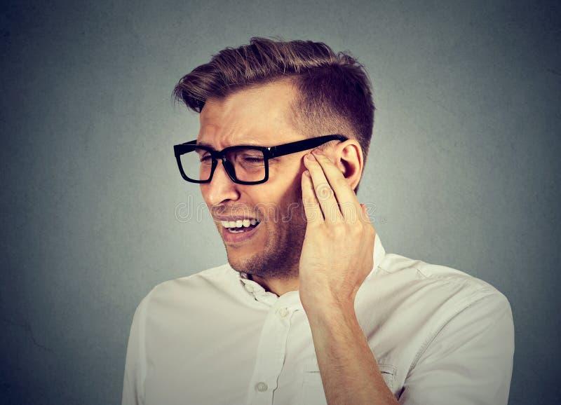 tinnitus Chory mężczyzna ma uszatego ból dotyka bolesną głowę obrazy royalty free
