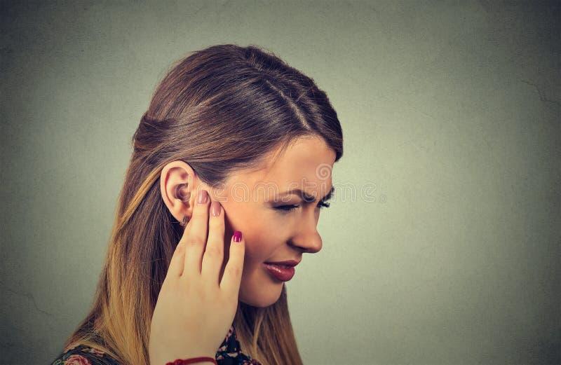 tinnitus den sjuka unga kvinnan som har örat, smärtar att trycka på hennes smärtsamma huvud arkivbilder