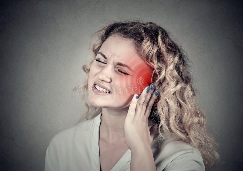 tinnitus Fêmea doente tendo a dor de orelha que toca em sua cabeça dolorosa imagem de stock