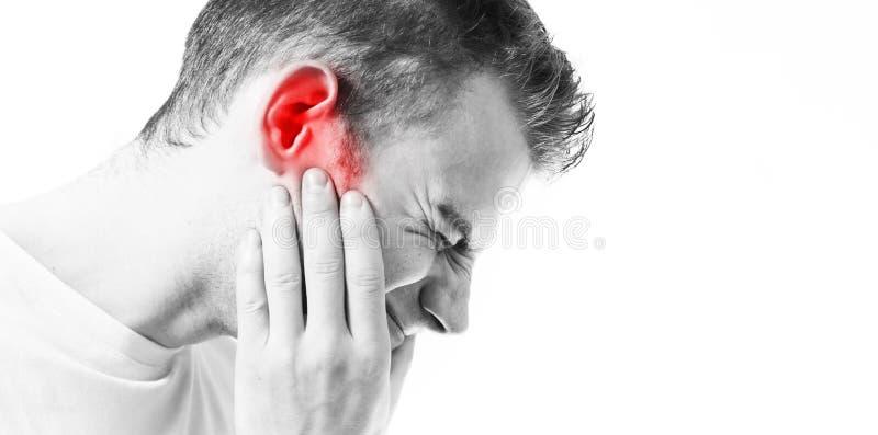 Tinnitus, homem em um fundo branco que guarda uma orelha doente, sofrendo da dor fotos de stock royalty free