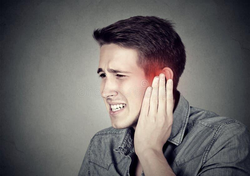 tinnitus Kranker Mann, der die Ohrschmerz berühren seinen schmerzlichen Kopf hat lizenzfreies stockbild