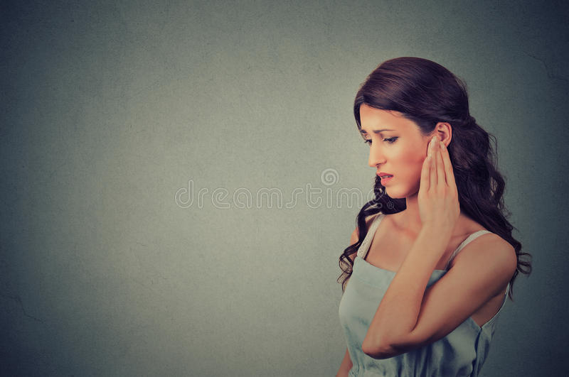 Tinnitus. Side profile sick young woman having ear pain touching her painful head royalty free stock photos