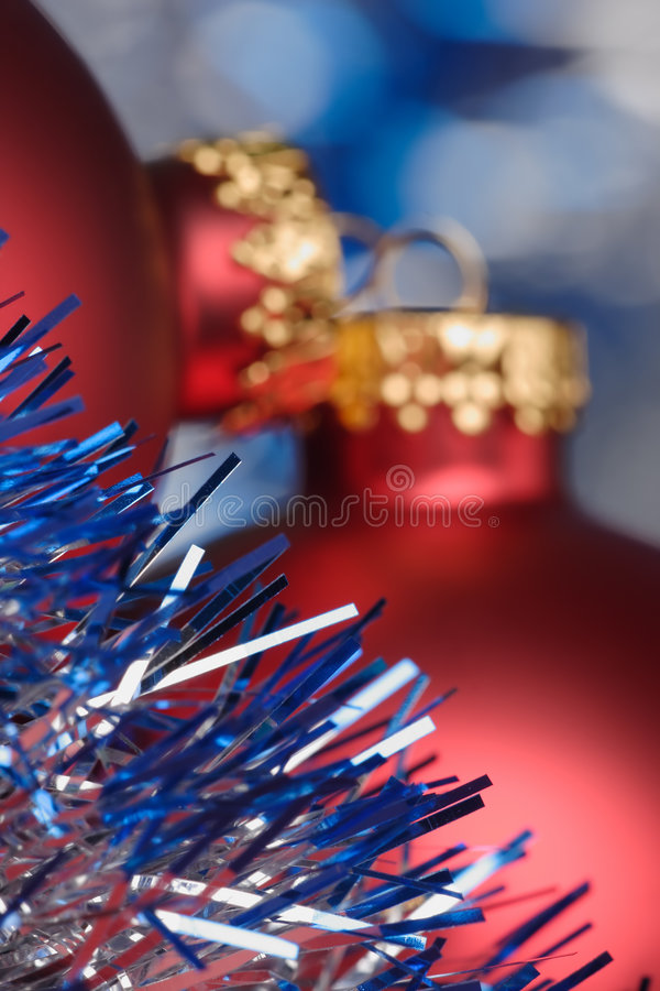 Tinsel and Christmas baubel. Blue/silver tinsel with out-of-focus red Christmas baubels in the background stock images