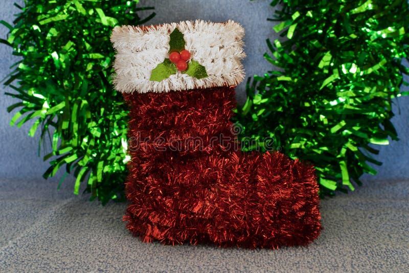 Tinsel Christmas strumpaprydnad med en grön glitterbakgrund fotografering för bildbyråer