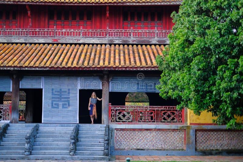 Tint/Vietnam, 17/11/2017: Vrouw die zich binnen een traditioneel huis met sier betegeld dak in de Citadel van Tint bevinden, Viet royalty-vrije stock afbeelding