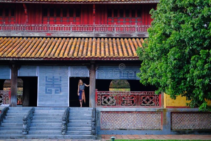 Tint/Vietnam, 17/11/2017: Vrouw die zich binnen een traditioneel huis met sier betegeld dak in de Citadel van Tint bevinden, Viet stock foto