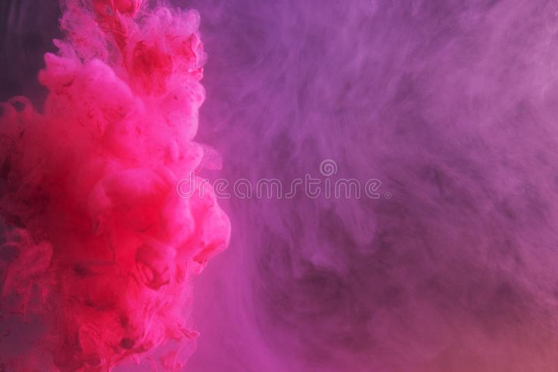 Tinta en agua Tinta que remolina en agua Tinta en el agua aislada Tinta rosada en agua en un fondo negro fotografía de archivo