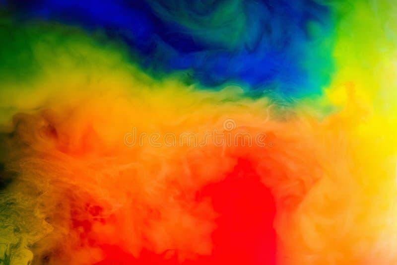 Tinta en el agua Chapoteo de la pintura roja, azul, amarilla y verde abstraiga el fondo fotografía de archivo libre de regalías