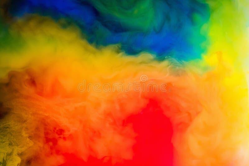 Tinta en el agua Un chapoteo de la pintura roja, azul, amarilla y verde abstraiga el fondo fotos de archivo libres de regalías