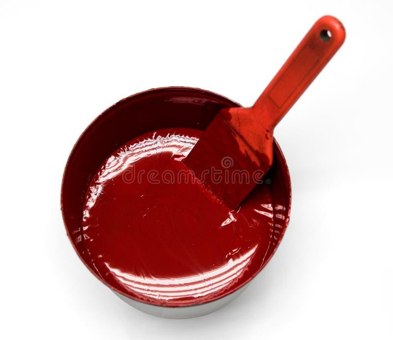 Tinta vermelha em uma lata com a escova no fundo branco fotos de stock