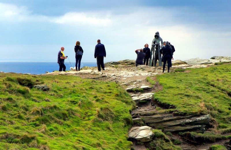 Tintagel, Cornwall, het UK - 10 April 2018: Toeristen die voor phot stellen stock fotografie