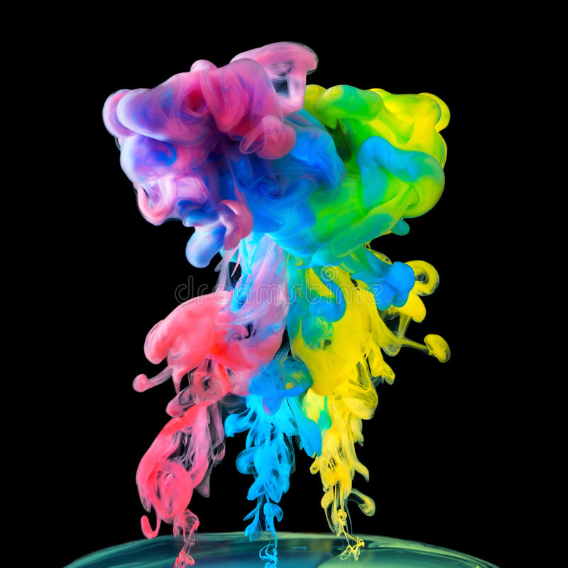 Tintas coloridas na água no fundo preto foto de stock