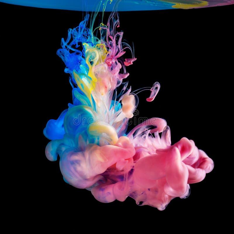 Tintas coloridas na água no fundo preto imagem de stock
