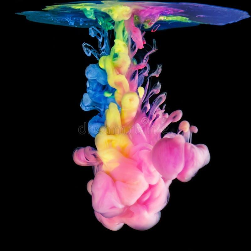 Tintas coloridas na água no fundo preto imagens de stock royalty free