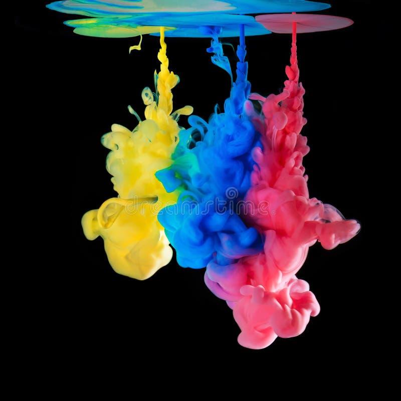 Tintas coloridas na água no fundo preto fotos de stock