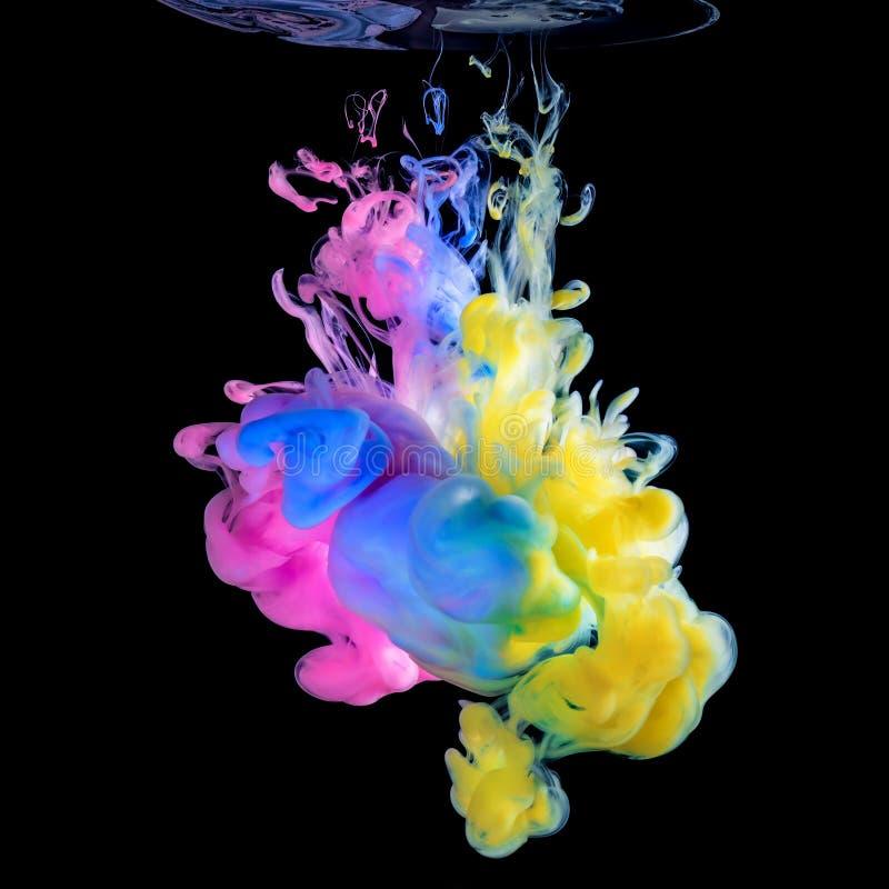 Tintas coloridas na água no fundo preto fotografia de stock