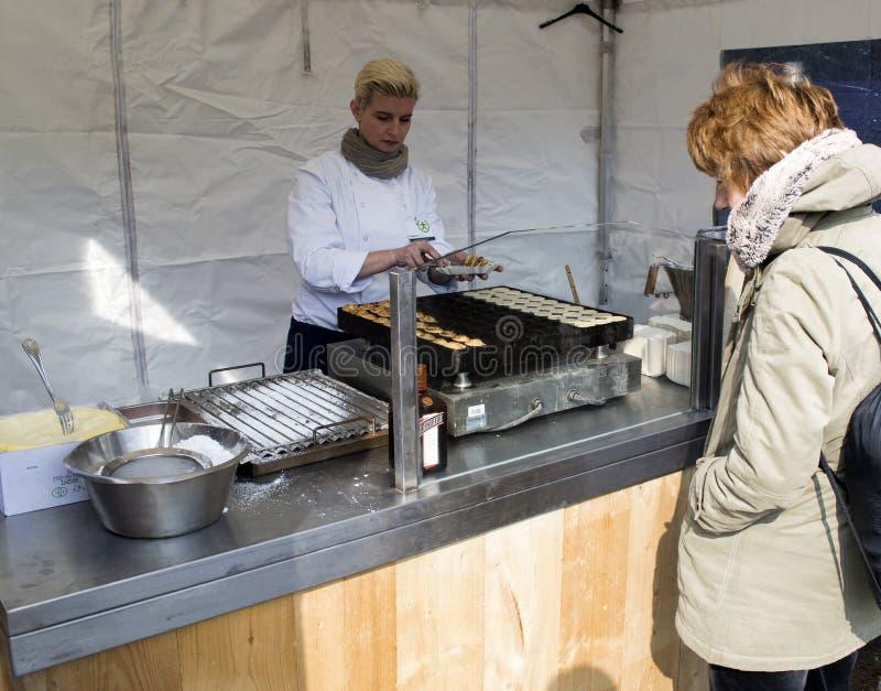 Kvinnan som säljer holländska pannkakor, kallade poffertjes fotografering för bildbyråer