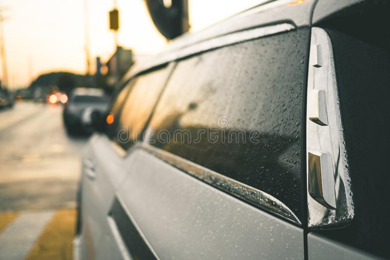 The tinted glass of the car is covered with drops after the rain. stock images