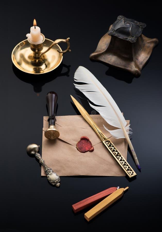 Tinteiro de bronze, escrevendo a pena, o selo do selo da cera, o abridor de letra e a cera de selagem imagens de stock royalty free