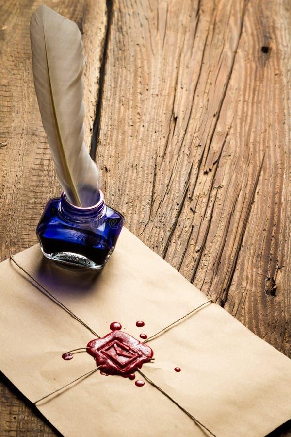 Tintenfaß der blauen Tinte mit Feder auf Umschlag mit rotem Dichtungsmittel lizenzfreie stockfotos