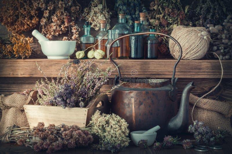 Tintflessen, gezonde kruiden, mortier, curatieve drugs, oude theeketel op houten plank stock fotografie