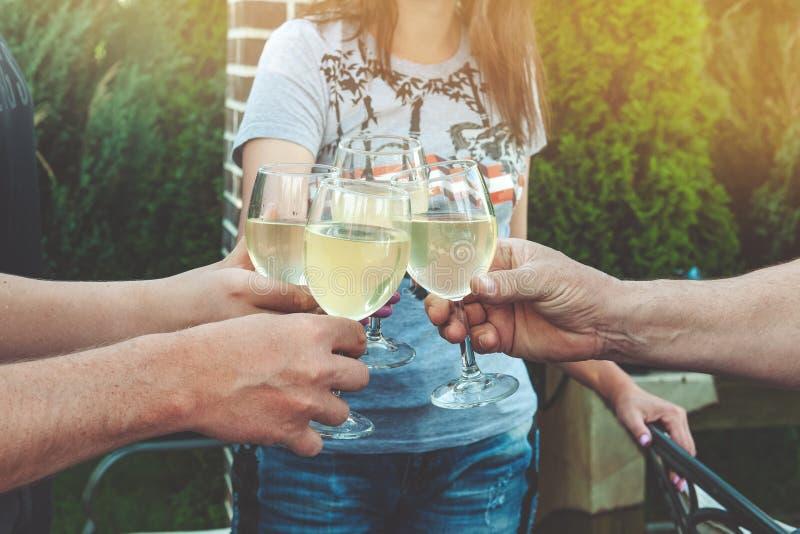 Tintineando los vidrios de vino blanco y de gente joven de la tostada celebre un cumpleaños en una comida campestre imagen de archivo