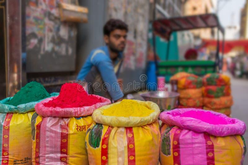 Tinturas pulverizadas coloridas da venda não identificada do homem usadas para o festival de Holi na Índia imagens de stock royalty free