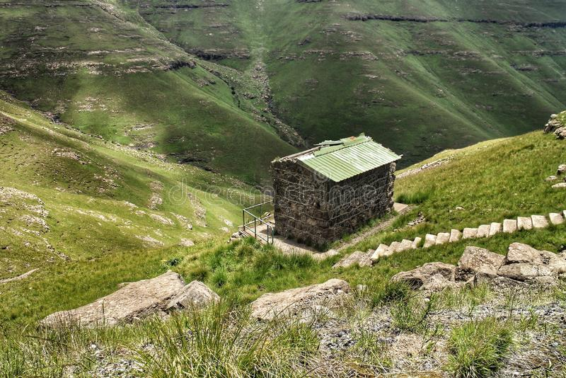 A tiny building next to a steep abyss in the Drakensberg mountains of Lesotho and South Africa. stock photo