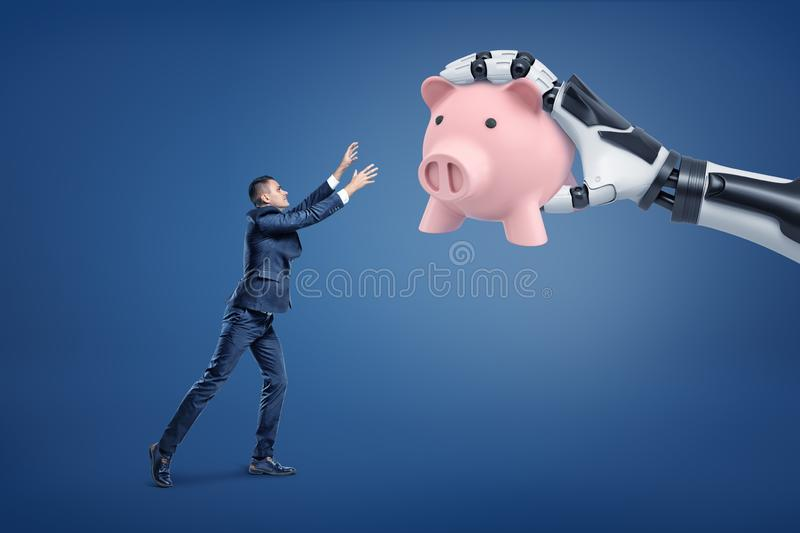 A tiny businessman loses a large pink piggy bank to a giant robotic hand. stock photo
