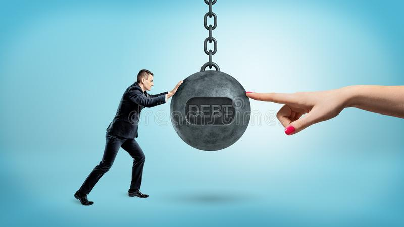 A tiny businessman pushes a large wrecking ball with a word DEBT against a giant female finger on the other side. stock photos