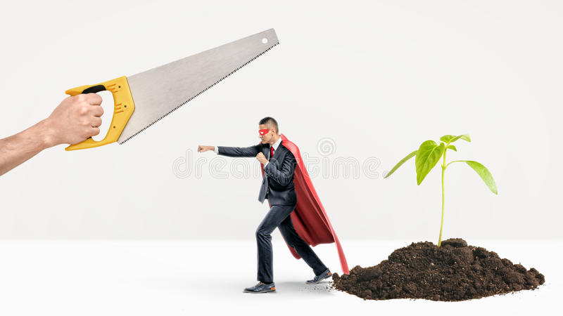 A tiny businessman in a red cape fighting off a giant hand with a saw while behind him a new plant grows. royalty free stock images
