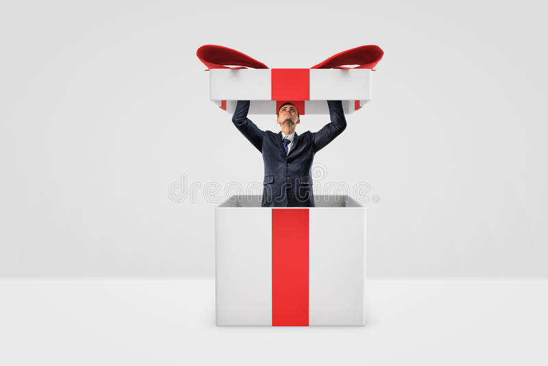 A tiny businessman standing inside a gift box and opening its lid with both hands. Ads and commercials. Best offers. Business promotion stock photo