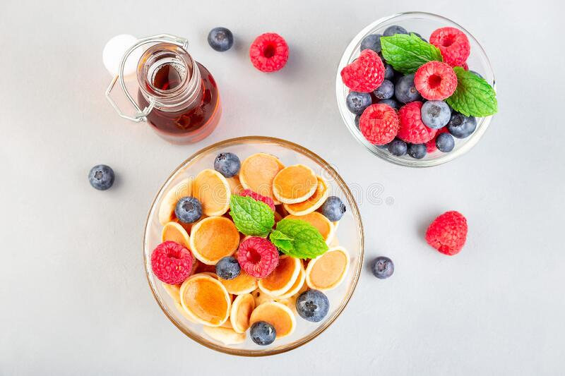 Tiny cereal pancakes served with maple syrup, raspberry and blueberry, in glass bowl, horizontal, top view royalty free stock image