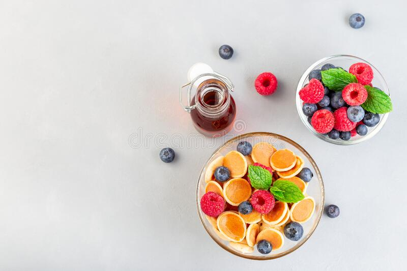 Tiny cereal pancakes served with maple syrup, raspberry and blueberry, in glass bowl, horizontal, top view, copy space stock photography