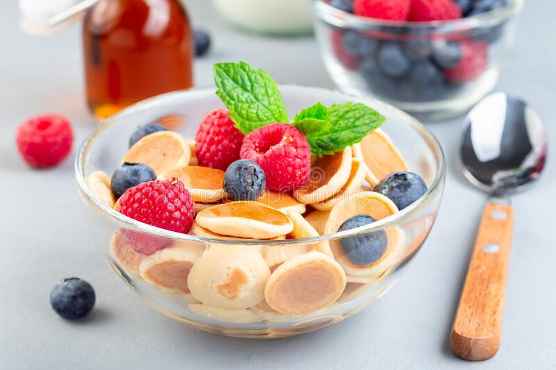 Tiny cereal pancakes served with maple syrup, raspberry, blueberry and milk, in a glass bowl, horizontal stock photos