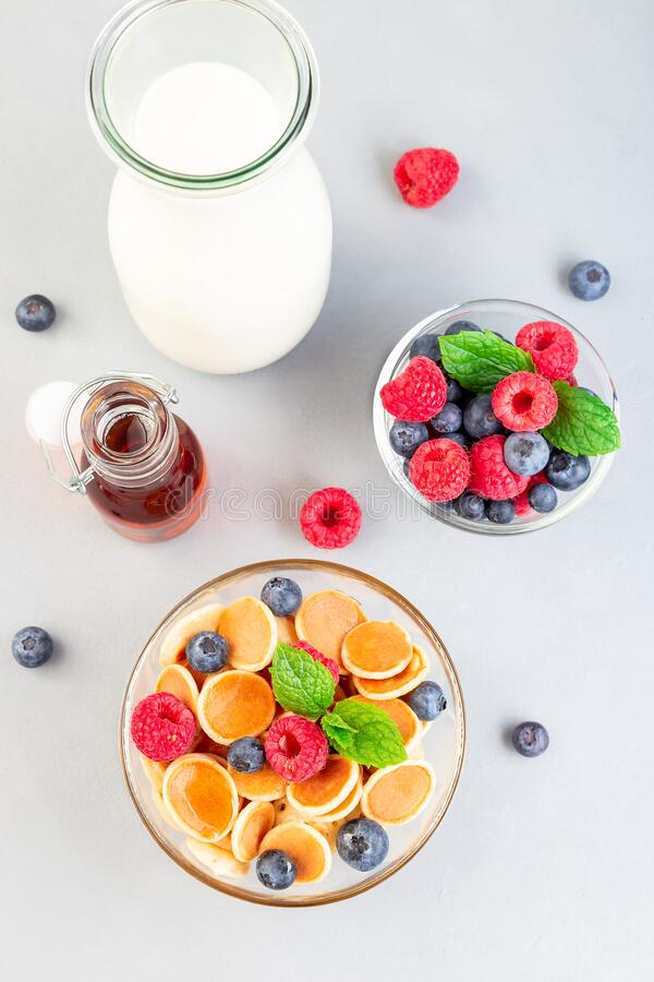 Tiny cereal pancakes served with maple syrup, raspberry, blueberry and milk, in glass bowl, vertical, top view royalty free stock photography