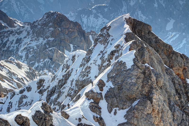 Tiny climbers ascend snowy Jubilaumsgrat route in Bavarian Alps. View of snowy climbing route Jubilaumsgrat from Zugspitze in Wetterstein range with two tiny royalty free stock images