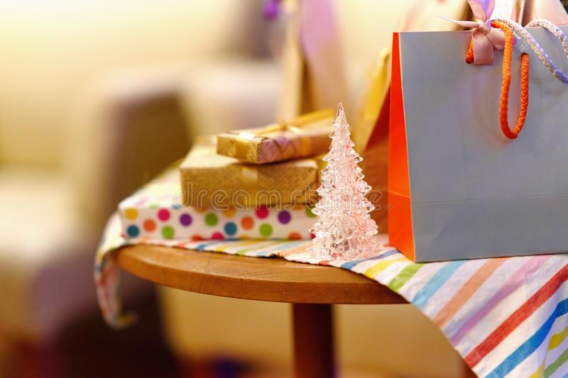 Tiny crystal christmas tree and present bags and boxes on table royalty free stock image