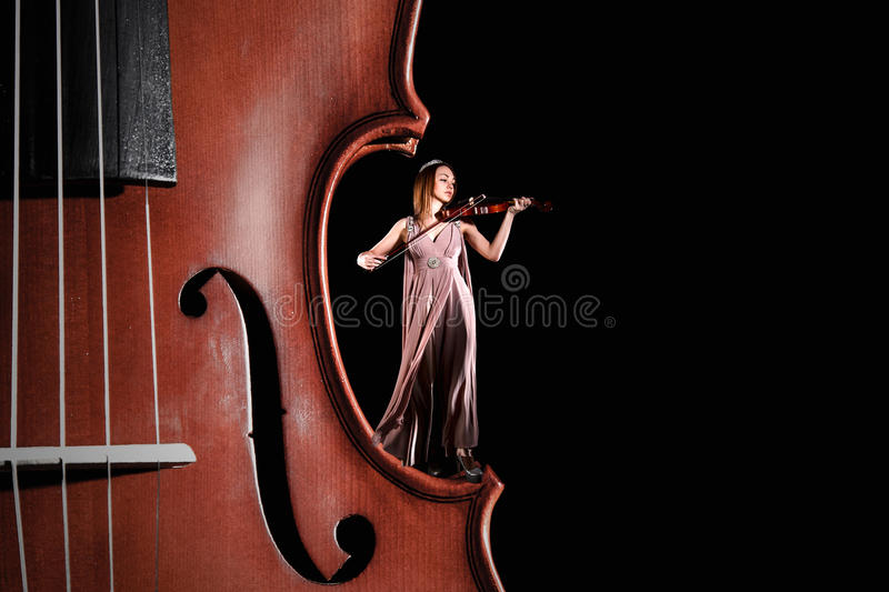 Tiny female violinist. Playing a violin staying on the edge of the big one over black background royalty free stock images