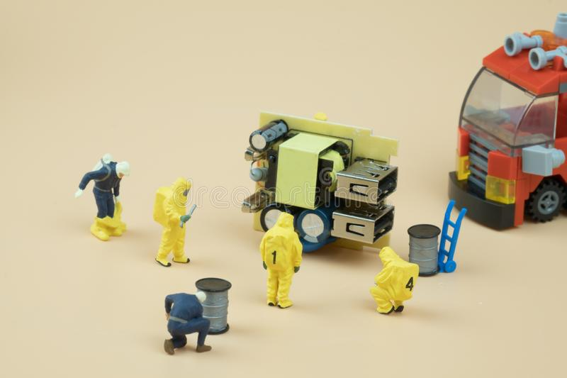 Tiny figures of chemical team in hazmat suits examining. Safety concept stock photography