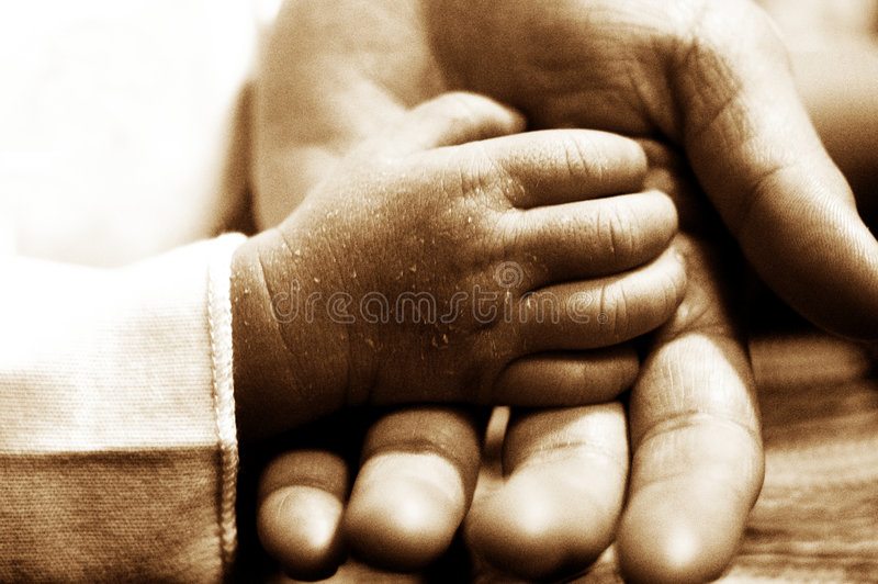 Tiny hands. New born baby hands playing. intentional shallow DOF. Intentional noise. Sepia toned stock photos