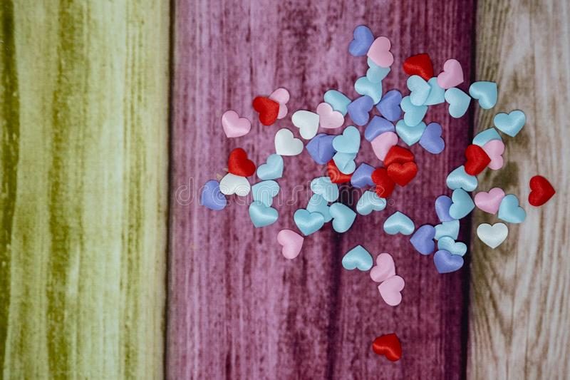Tiny hearts in pink, blue, purple and red colors over a colorful wooden background. Useful for headers and banners with extra text royalty free stock photos