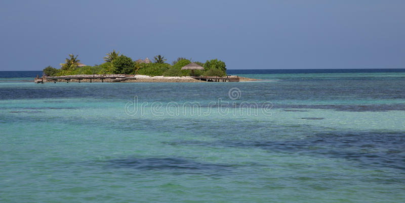 Tiny islet in turquoise waters of Maldives stock image