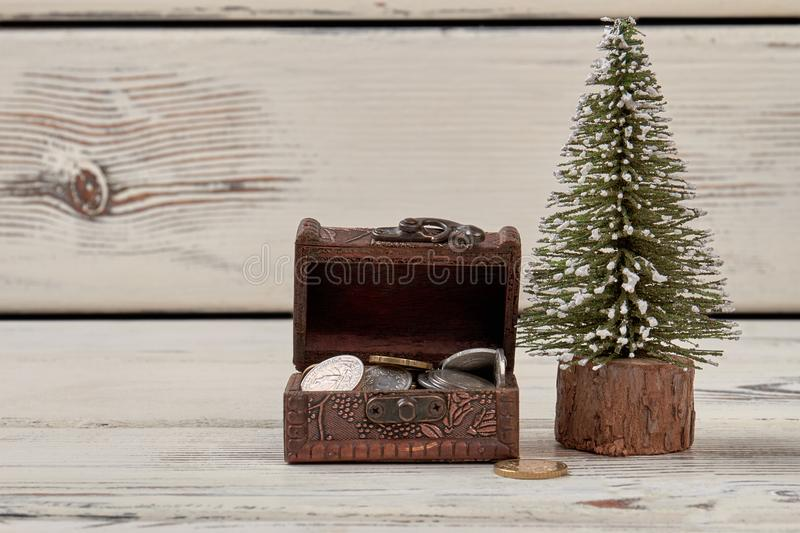 Tiny jewelry box with coins and christmas tree. stock images