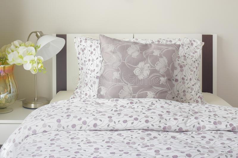 Tiny lavender pattern style bedding in bedroom with white orchid stock photography