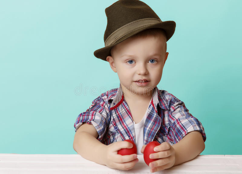 Tiny little boy in a hat looks on viewer in hands holding red Ea stock image