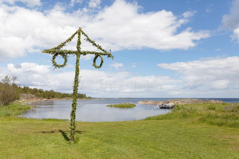 Tiny maypole in the Swedish archipelago, blue sky and white clou stock images